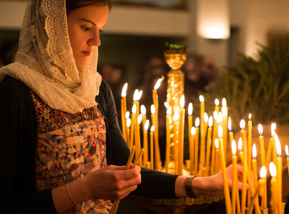 A member of the congregartion lights a candle during a midnight mass vigil at the Russian Orthodox Church Abroad's 'Cathedral of the Dormition of the Mother of God and the Royal Martyrs' Church in London