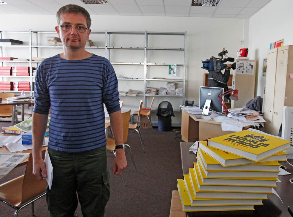 French cartoonist Charb, publishing director of French satirical weekly Charlie Hebdo, poses for photographs at their offices in Paris, September 19, 2012