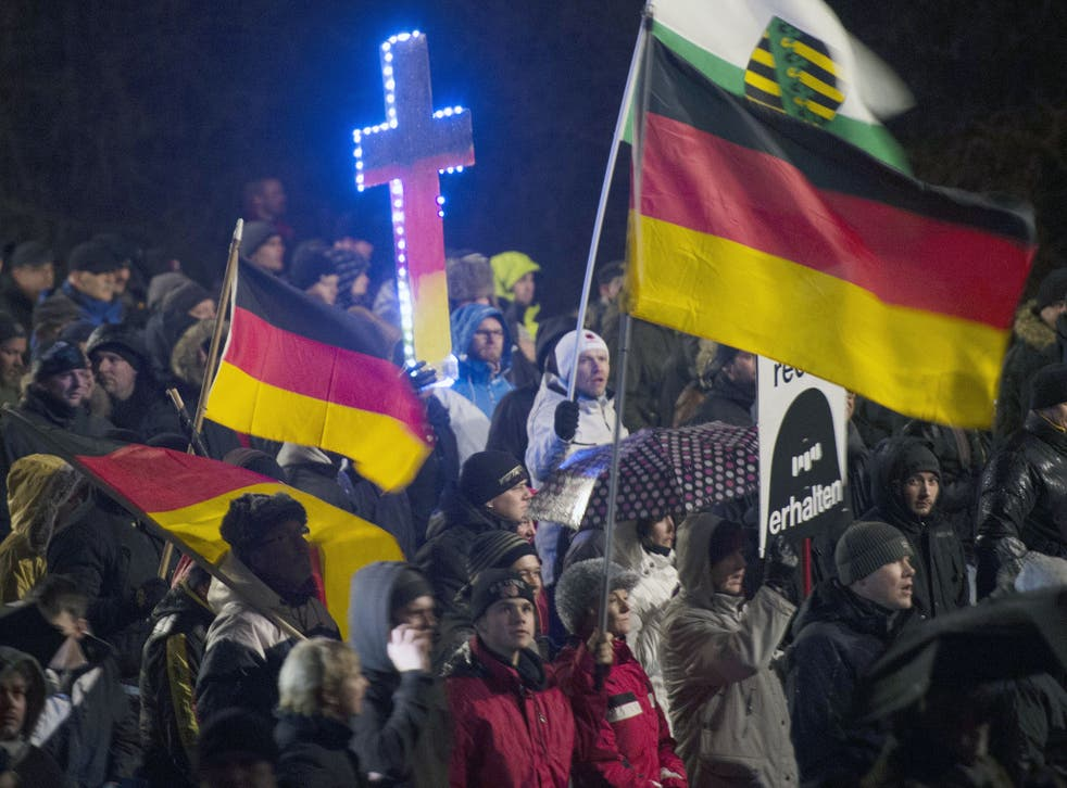 A demonstrator holds a crucifix (C) in the colors of Germany during a rally by a mounting right-wing populist movement called Pegida in Dresden