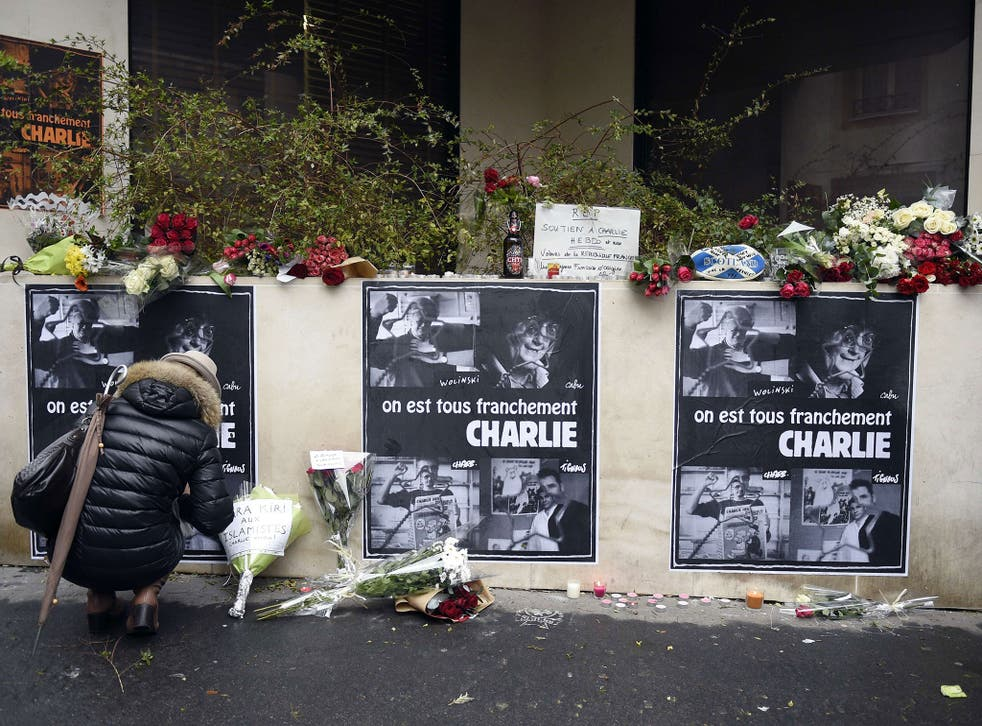 A woman places flowers near the offices of French satirical newspaper Charlie Hebdo in Paris