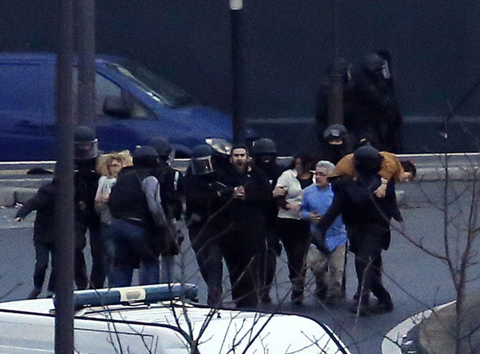 Members of the French police special forces evacuate the hostages after launching the assault at a kosher grocery store in Porte de Vincennes, eastern Paris