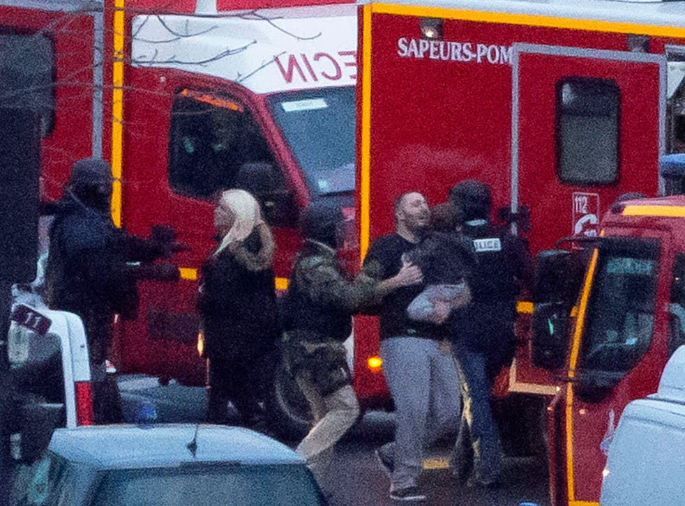 A security officer directs released hostages after they stormed a kosher market to end a hostage situation