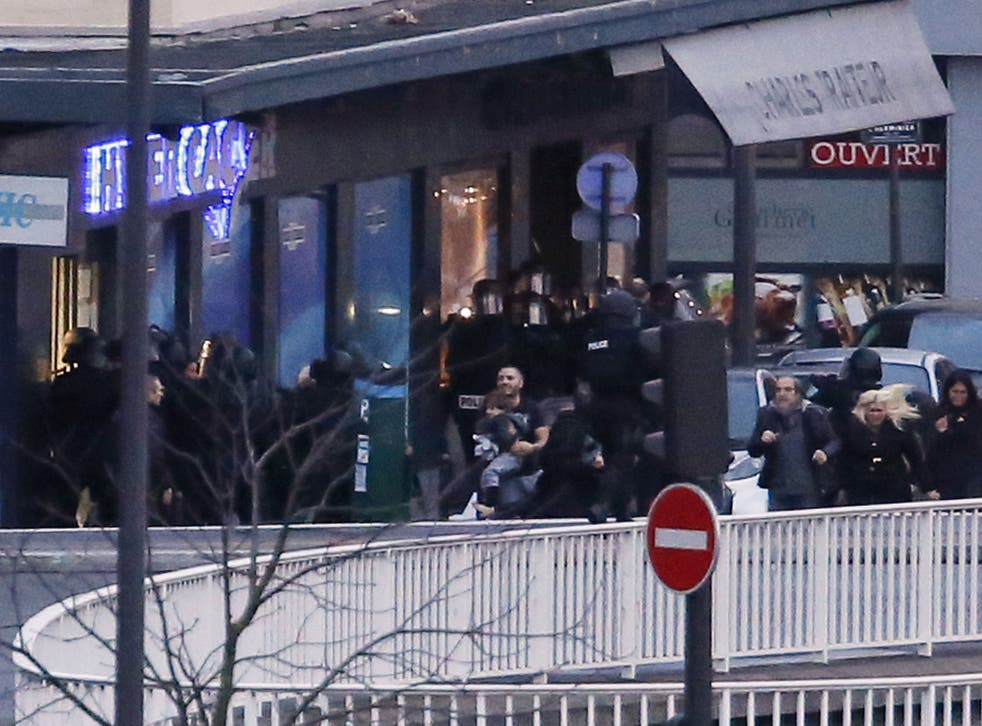 Members of the French police special forces evacuate the hostages including a child (C) after launching the assault at a kosher grocery store in Porte de Vincennes, eastern Paris