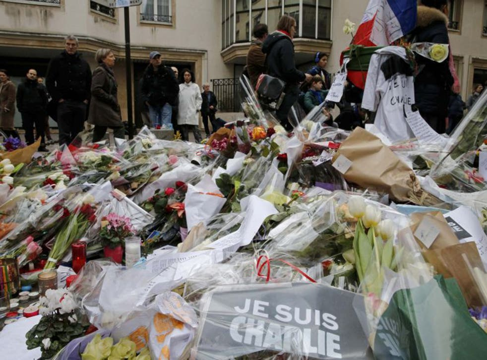 Flowers and messages lie in tribute in front of the offices of the weekly satirical newspaper Charlie Hebdo on Saturday (Reuters)