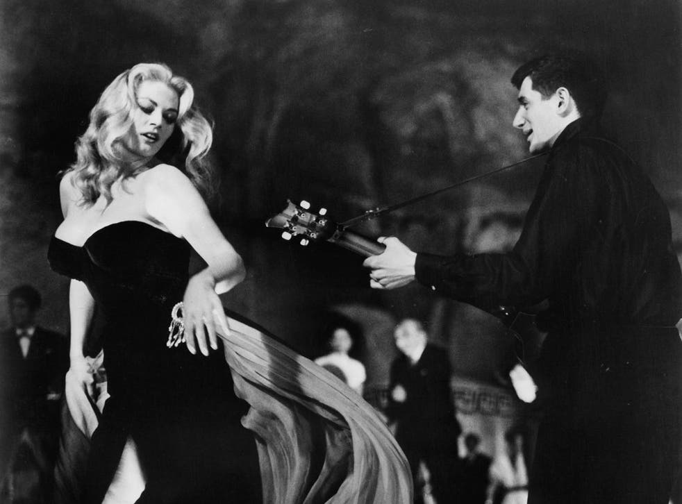 Anita Ekberg dancing to guitarist in a scene from the film
