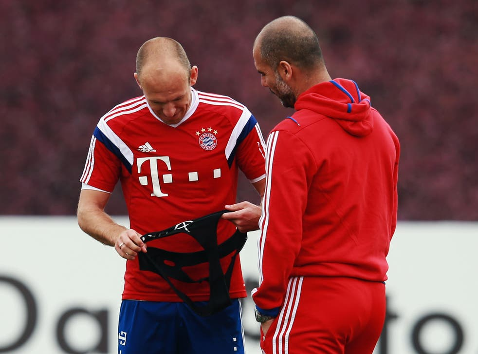 Head coach Pep Guardiola talks to Arjen Robben in Doha