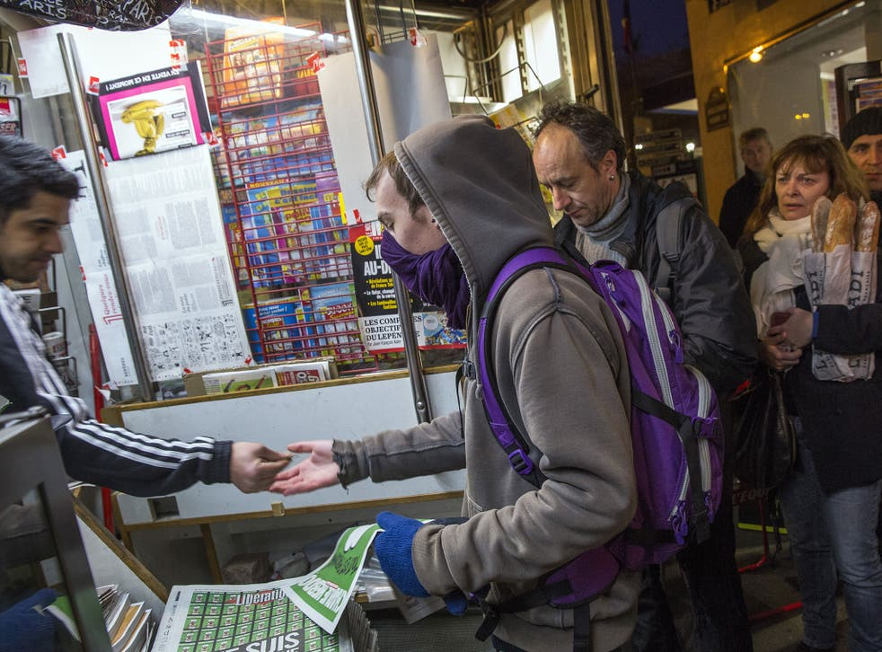 Parisians queue to buy the latest copy of Charlie Hebdo magazine, the first since gunmen killed eight of its staff