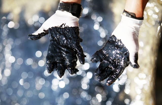 Oil covers the hands of a worker at the site of a spill in Cyprus