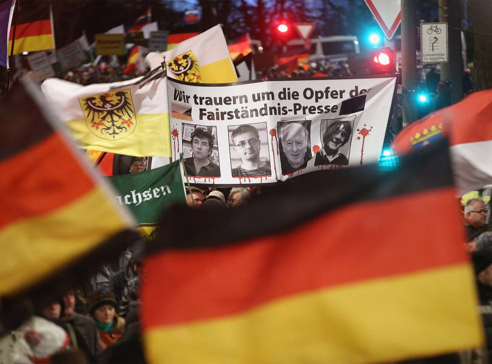 Thousands of supporters of the Pegida anti-Islamic movement march in Dresden on Monday with a banner showing the employees murdered in the attack on 'Charlie Hebdo' offices in Paris