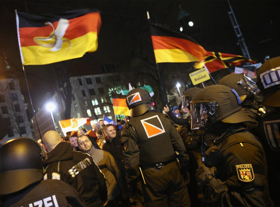Supporters of the Pegida movement wave German flags during their protest in Dresden, Germany, on Monday