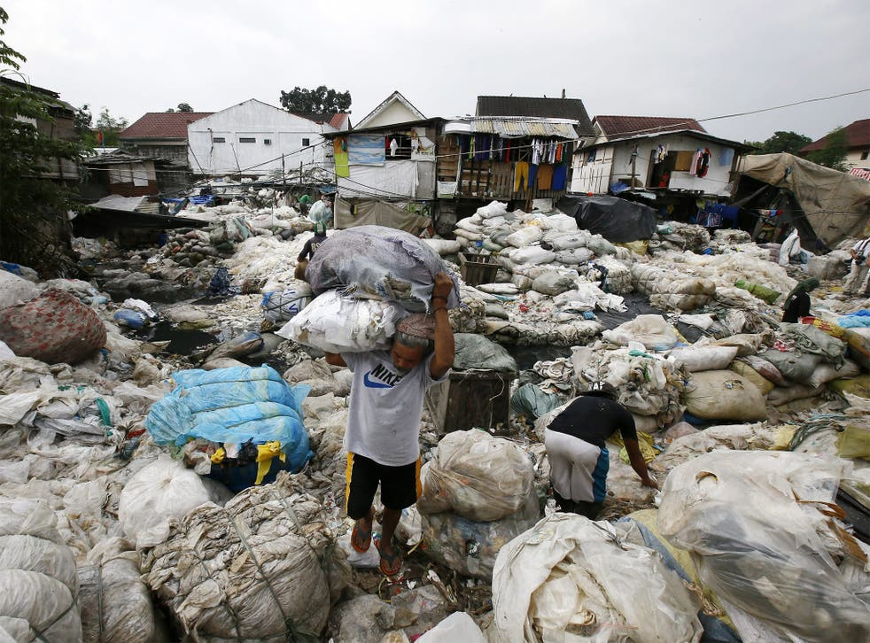 A Filipino man collects recyclable food at a dump site in Manila
