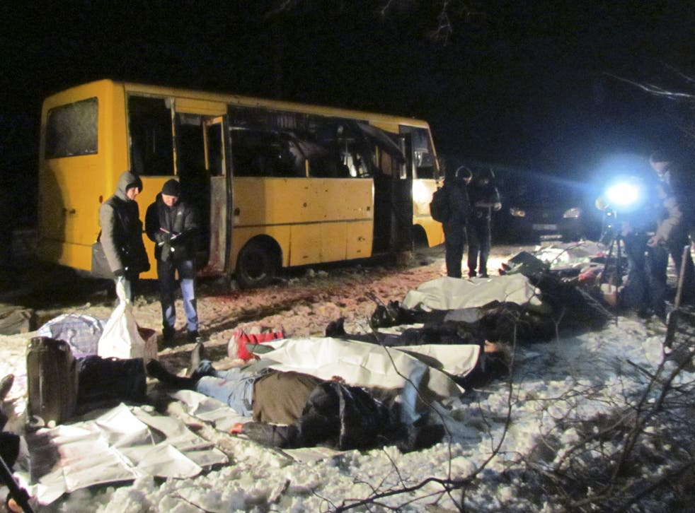 The bodies of the victims of a shelling attack on a bus near the Ukraine town of Volnovakha on Tuesday are laid out by the side of the Donetsk-Mariupol road