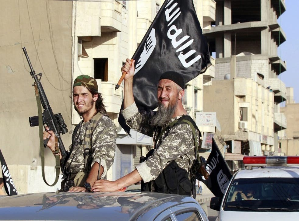Isis fighters wave flags as they take part in a military parade along the streets of Syria's northern Raqqa province
