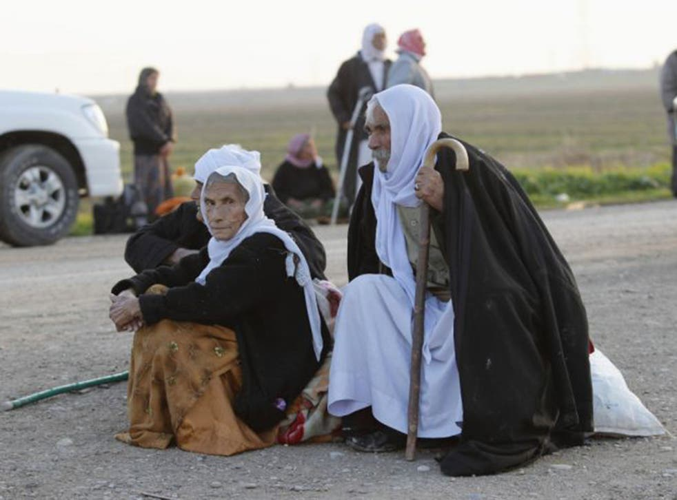 Elderly members of the Yazidi sect wait beside a road near Kirkuk after being released by their Isis captors on Saturday. They report continuing mistreatment of those still held captive (Reuters)