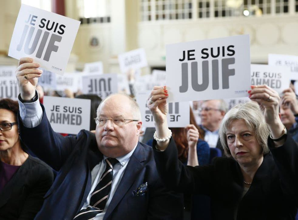 Theresa May and Eric Pickles, the Secretary of State for Communities, hold 'I am Jewish' signs at the event (Re