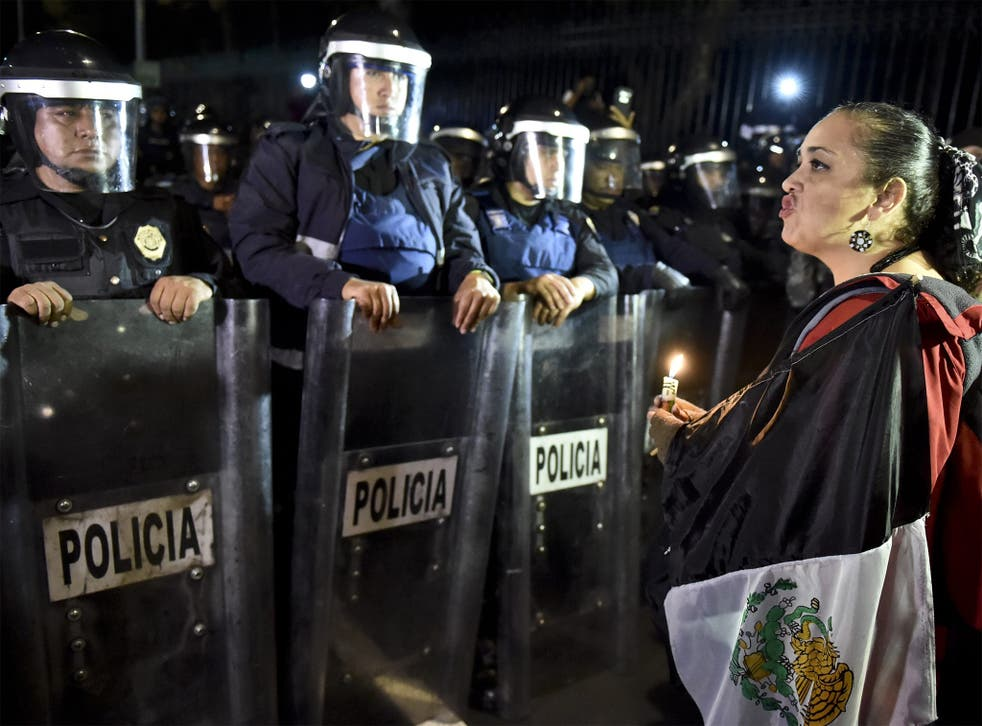 A woman protests outside the presidential palace in Mexico City to demand answers over the missing students in Guerrero state