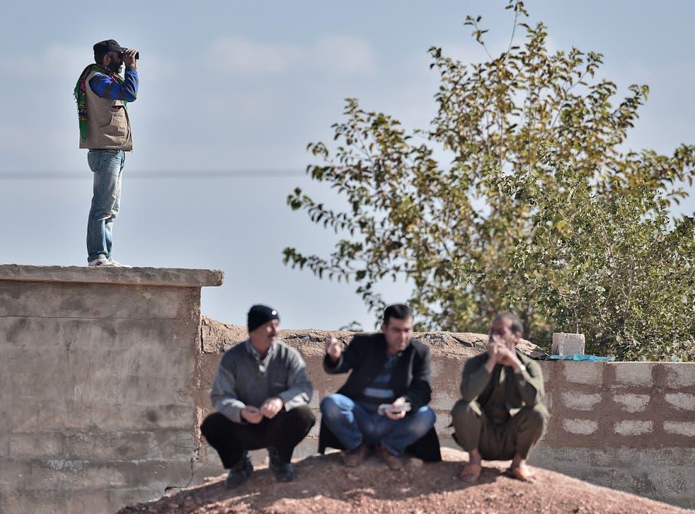 Kurdish men in the Turkish border village of Mursitpinar, overlooking the besieged Syrian city of Kobane in November last year