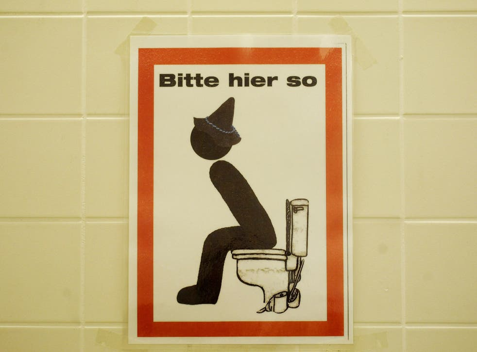 """A sign reading """"Bitte hier so"""" (please like this here) and depicting a seated man with bavarian hat on a toilet"""