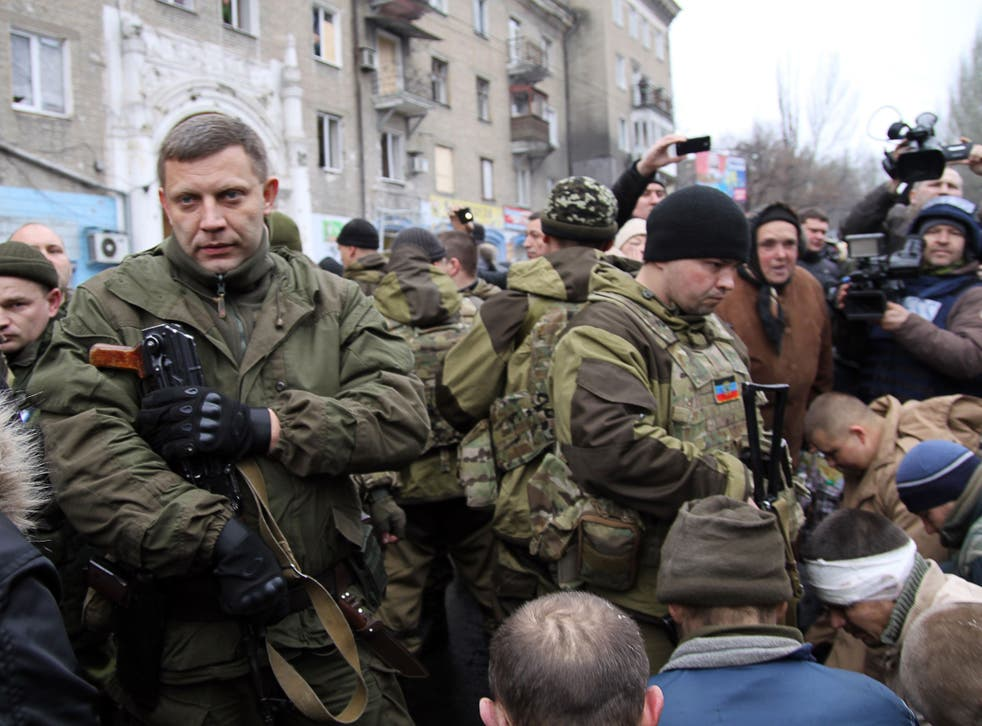 The leader of the self-declared Donetsk People's Republic Alexander Zakharchenko (on left) next to kneeling captive Ukrainian soldiers at a bus stop where 13 people were killed