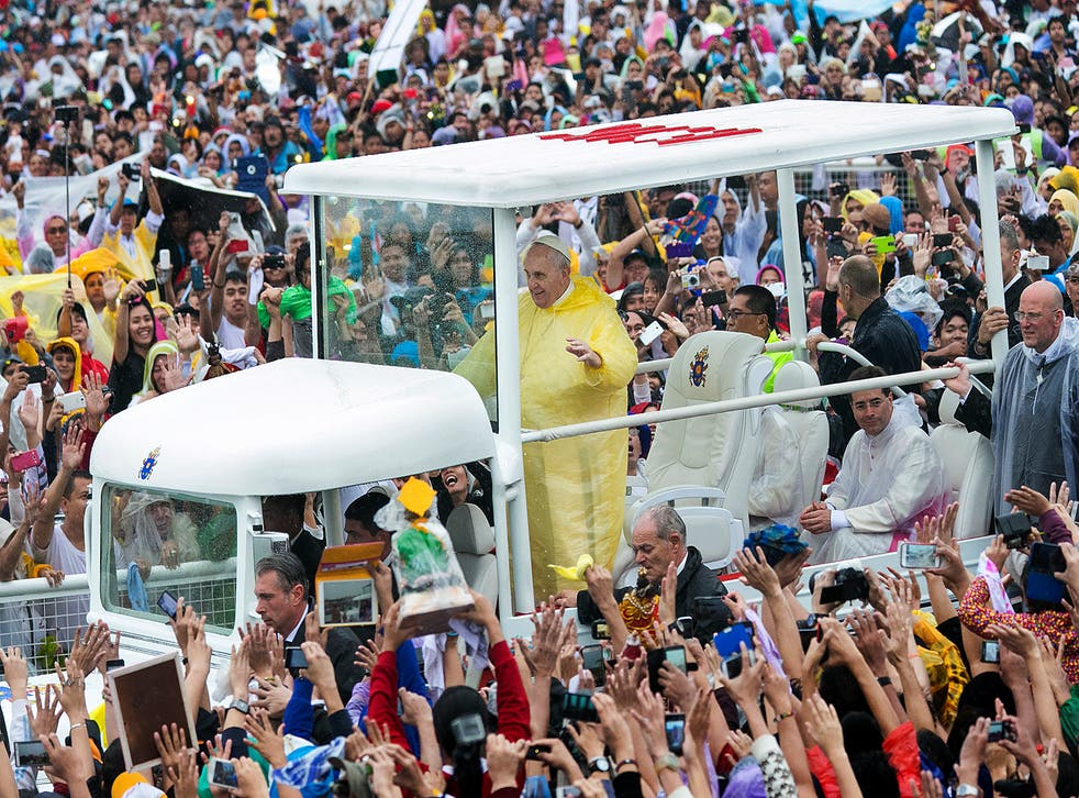 Pope Francis waves to the crowd as he arrives at Quirino Grandstand to celebrate his final Papal Mass in Manila