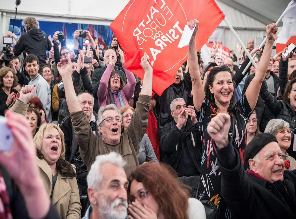 Supporters of the radical opposition party Syriza celebrate after the initial exit poll results for Greece's general elections are revealed