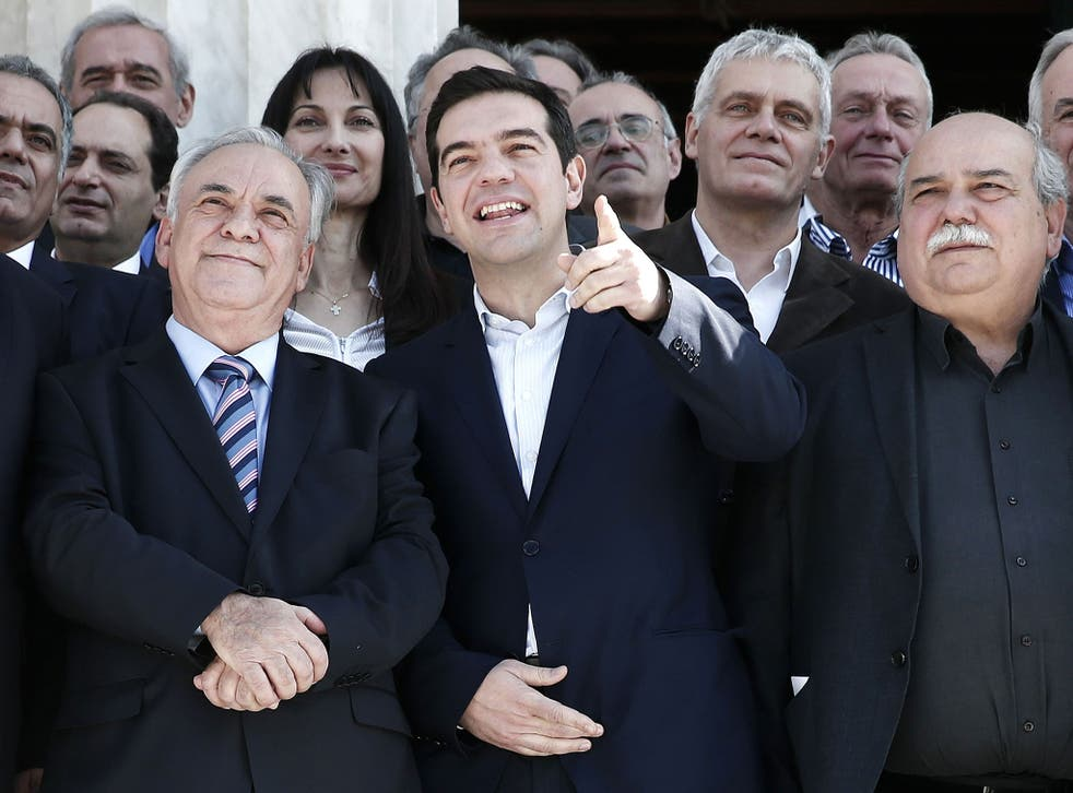 Greek Prime Minister Alexis Tsipras (centre) gestures next to Deputy Prime Minister Yannis Dragasakis (left) and Interior and Administrative Reconstruction Minister Nikos Voutsis after the first meeting of the new cabinet on January 28, 2015