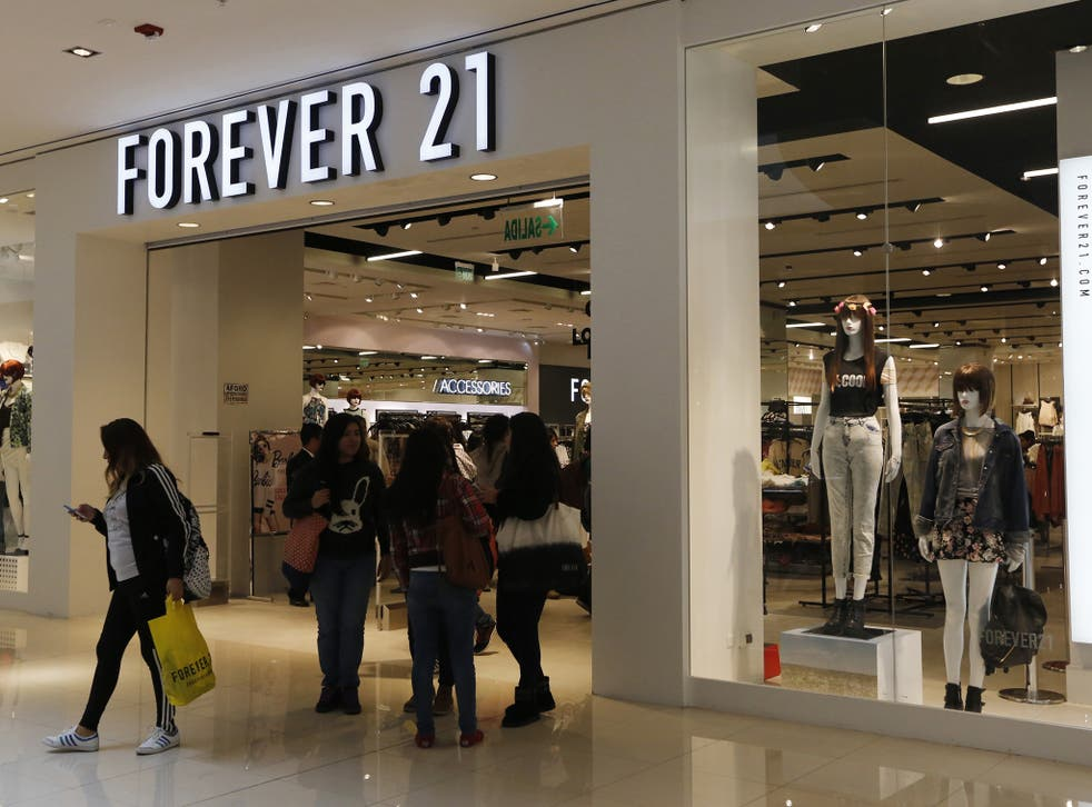 Customers walk and stand outside the first Forever 21 retail store in Lima, at Real Plaza Salaverry shopping mall October 1, 2014.