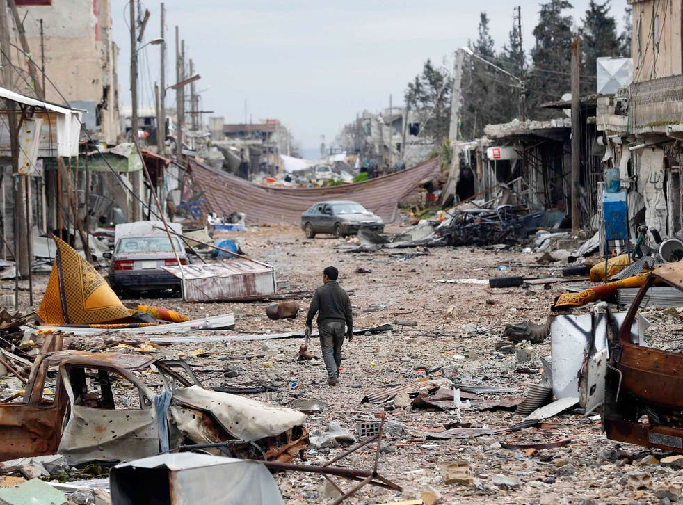 A man walks in a street with abandoned vehicles and and damaged buildings in the northern Syrian town of Kobani