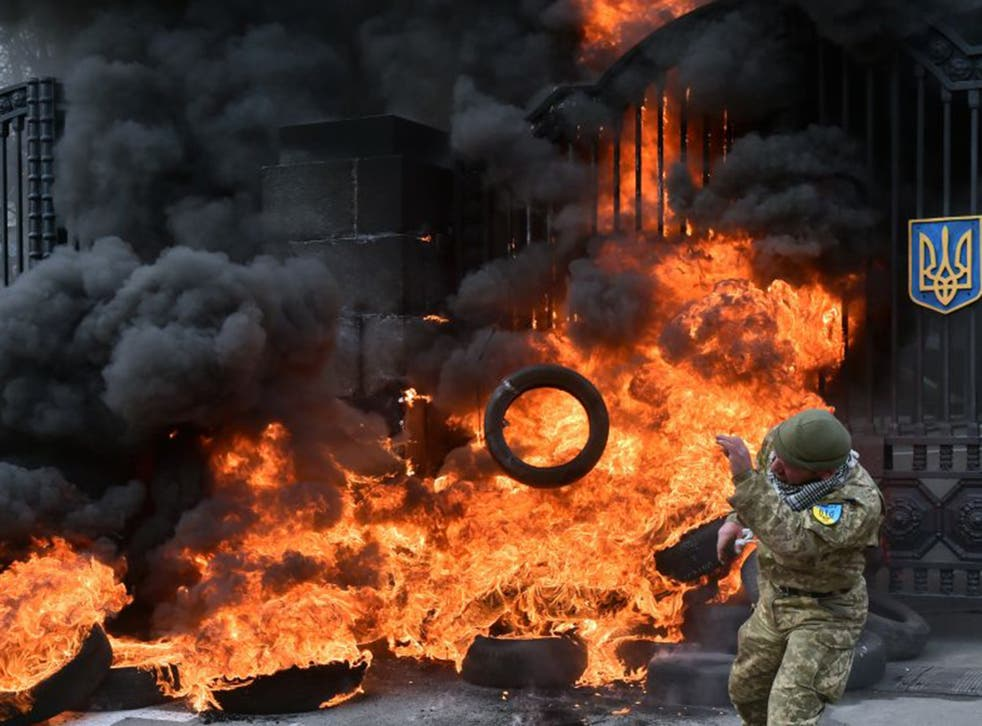 Fighters from the Aydar Ukrainian volunteer battalion burn tyres at the entrance to the Ukrainian Defence Ministry during demonstrations against their possible disbandment in Kiev on Monday (AFP/Getty)