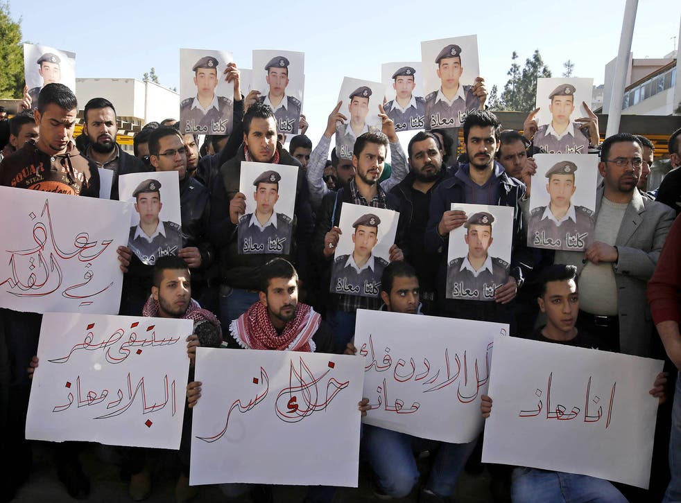 Supporters of Jordanian pilot Lt. Muath al-Kaseasbeh hold posters of him with Arabic that reads: 'We are all Muath' during a protest in Amman, Jordan
