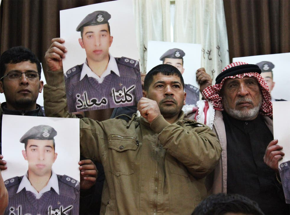 Relatives of Jordanian pilot Moazal al-Kasaesbeh hold his poster as they take part in a rally in his support at the family's headquarters in the city of Karak, last week