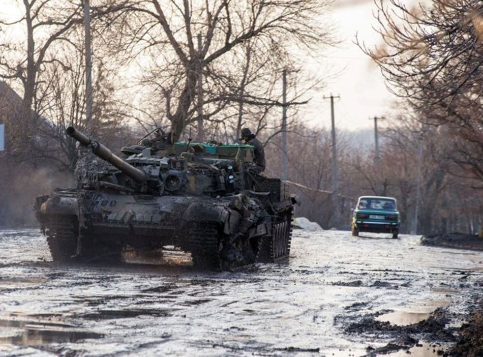 An armoured vehicle pulls a Ukrainian tank in the village of Horlivka, Donetsk region, on February 4, 2015, after it was damaged during combat between the Ukrainian forces and pro-Russian separatists.