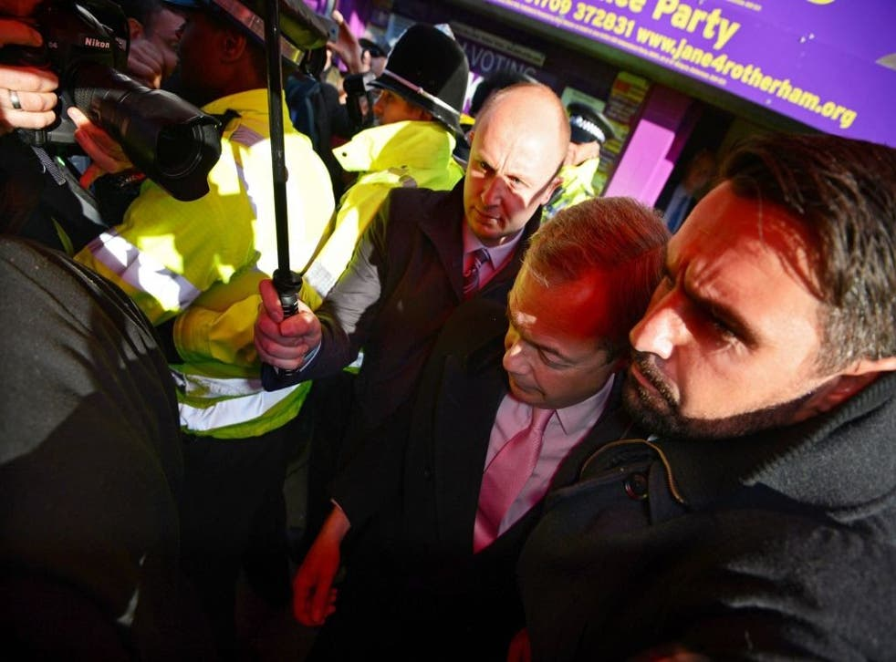 Nigel Farage is escorted out of the building in Rotherham with police help