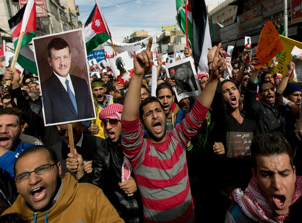 Demonstrators chant anti-Islamic State group slogans and carry posters with pictures of Jordanian King Abdullah II, late King Hussein and slain Jordanian pilot, Lt. Muath al-Kaseasbeh, during an anti-IS group rally in Amman, Jordan