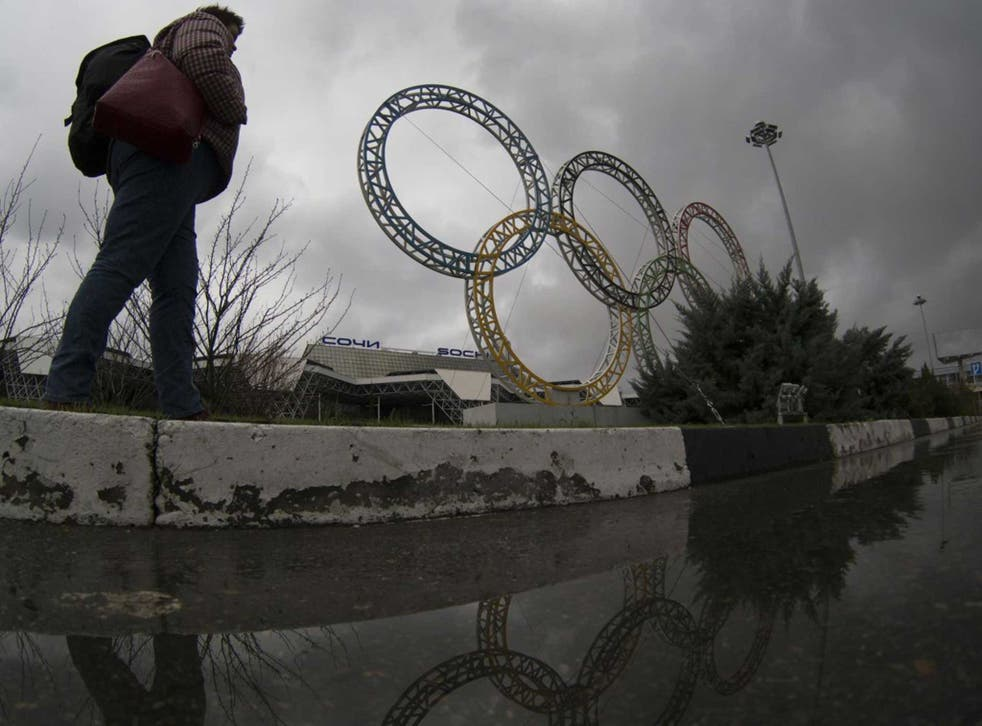 A woman walks past the seemingly abandoned Sochi grounds