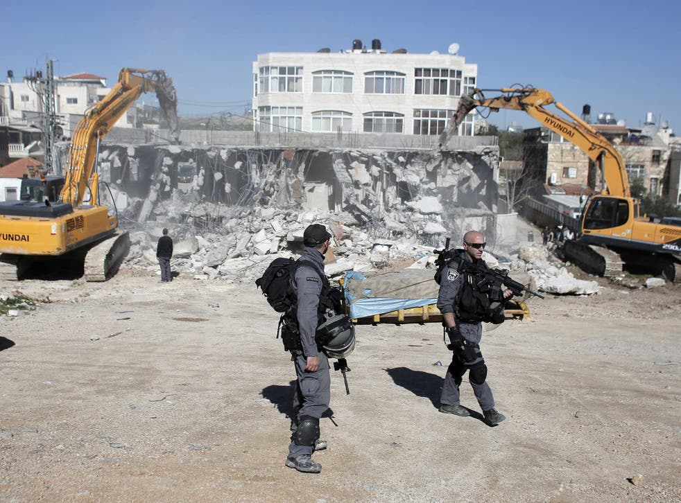 Members of the Israeli security forces stand guard as bulldozers hired by the Jerusalem municipality destroy a Palestinian house