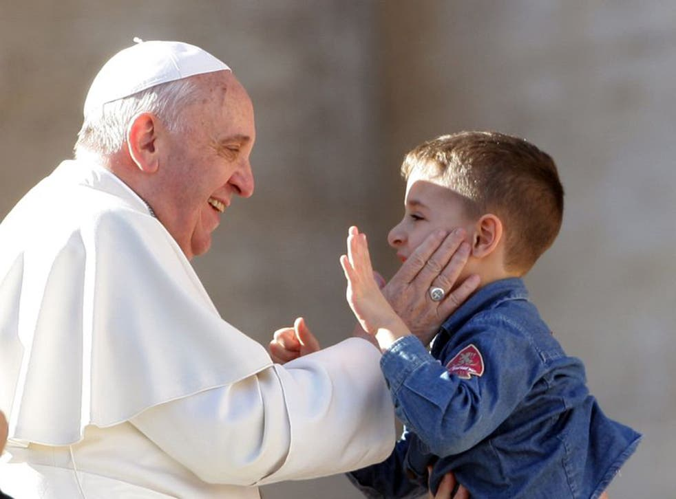 Smacking with dignity: Pope Francis greets a child last year