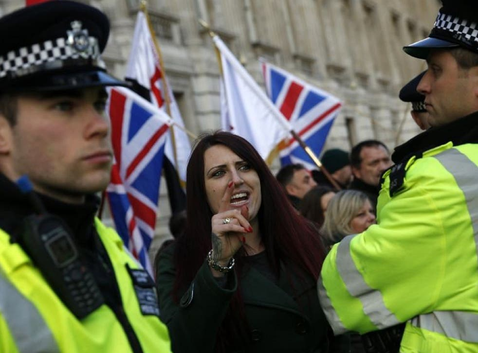 A Britain First member being watched over by police officers