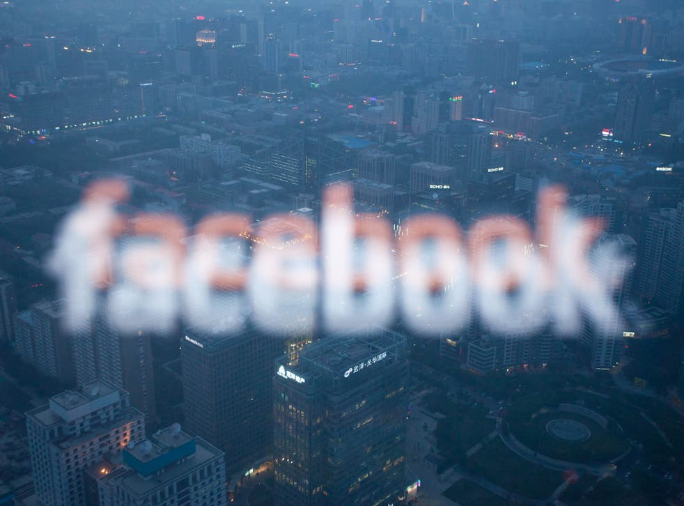 A photo taken on May 16, 2012 shows a computer screen displaying the logo of social networking site Facebook reflected in a window before the Beijing skyline