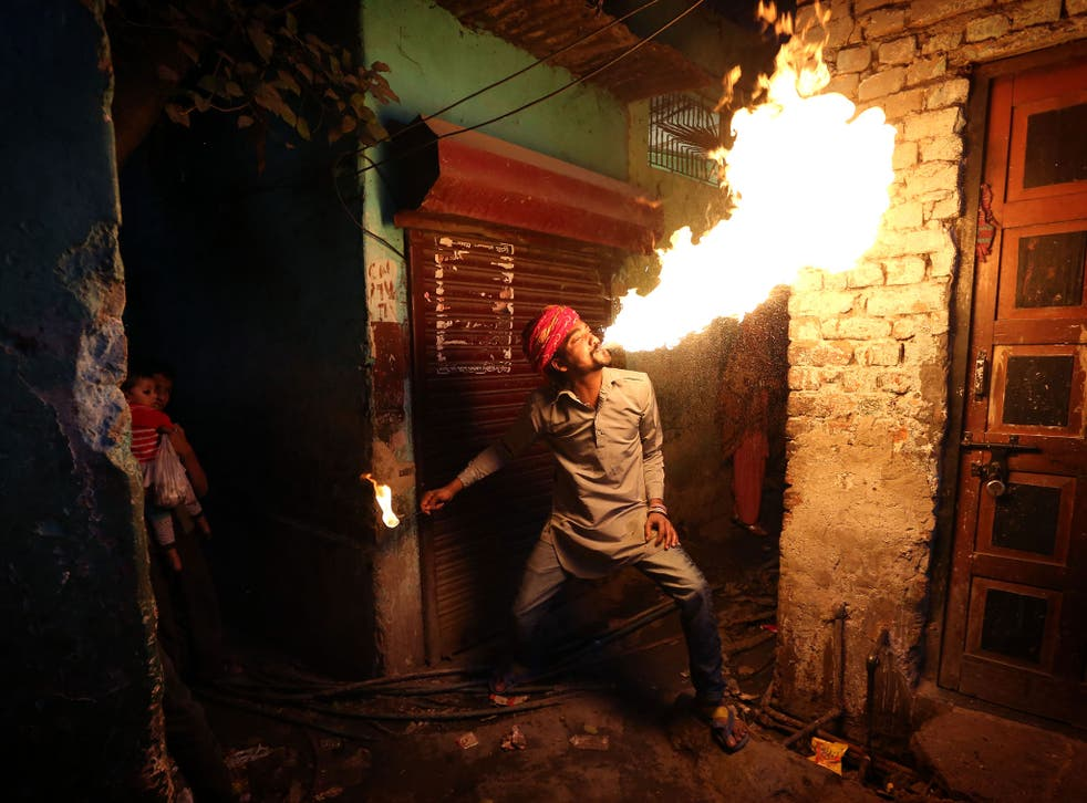 Fire breather Amit Kumar Bhatt practising his craft at his home in the Kathputli colony