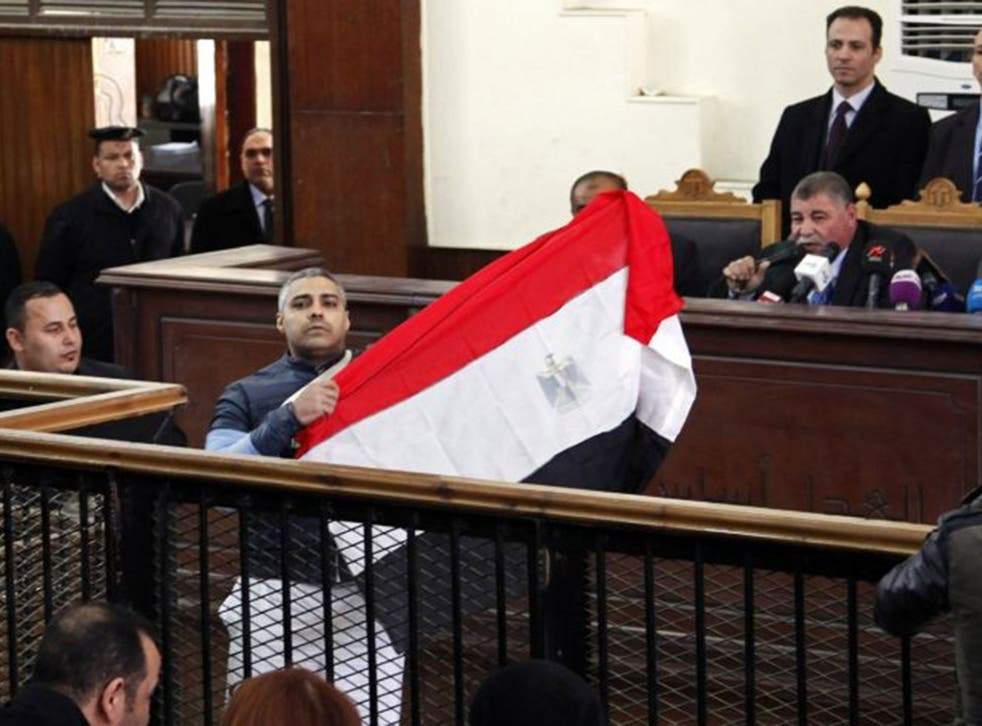 Al Jazeera journalist Mohamed Fahmy raises an Egyptian national flag while talking to the judge during his retrial at a court in Cairo February 12, 2015.