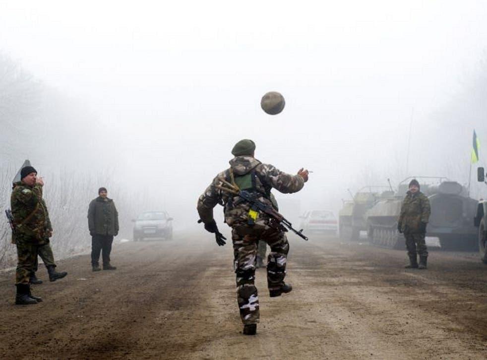 Ukrainian servicemen play football on a road at Svitlodarsk during the ceasefire
