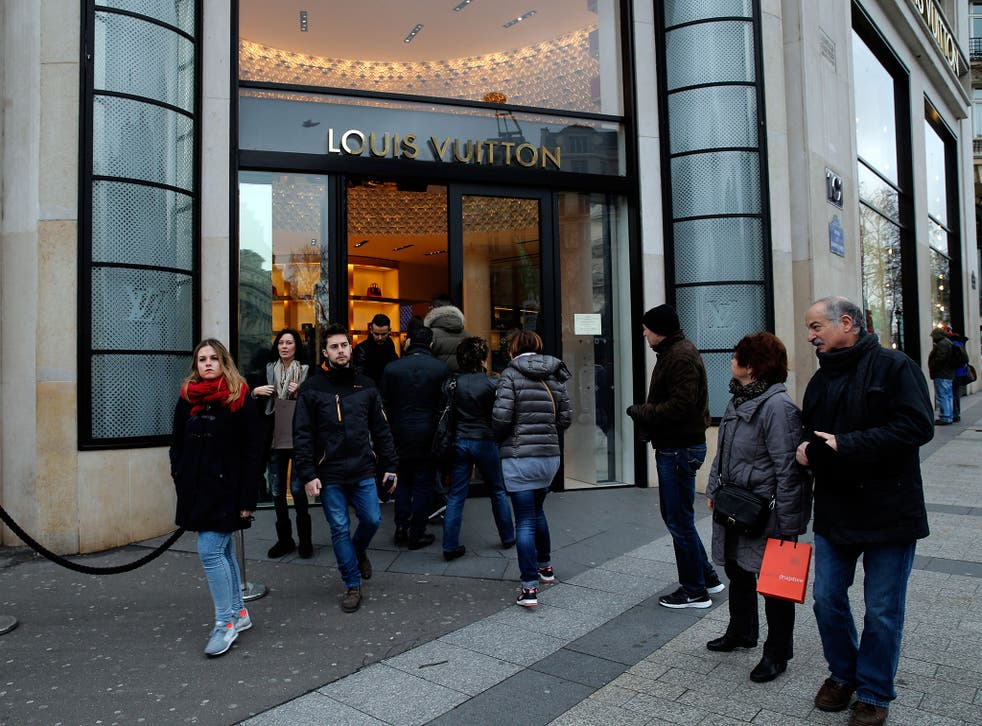 Shoppers enter a store on the Champs Elysees avenue, in Paris. France's lower house of parliament has approved a set of measures allowing more stores to open on Sundays and evenings, especially in touristy areas