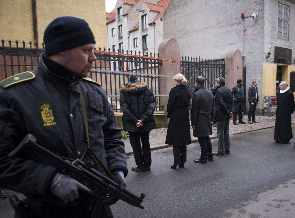 Danish Prime Minister Helle Thorning-Schmidt, third left, and Jewish community leaders pay their respects outside the synagogue in Krystalgade