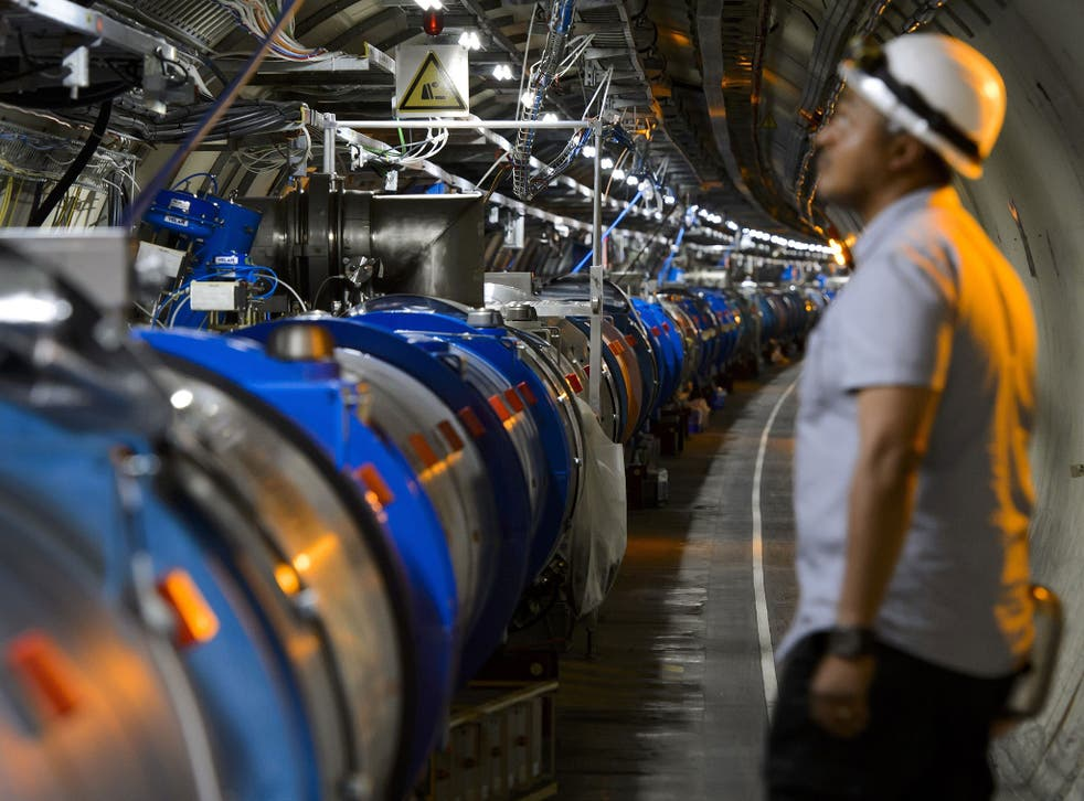 A scientist looks at a section of the Cern Large Hadron Collider during maintenance works in 2013 in Meyrin