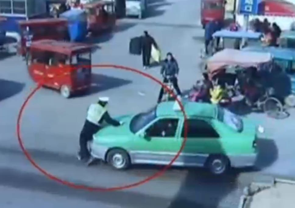 Video: Policeman dragged on car's bonnet for 300 metres as taxi