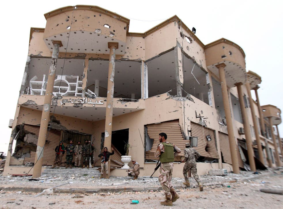 Libyan National Army fighters stand at the entrance of a destroyed building after clashes with Isis in Benghazi, last December