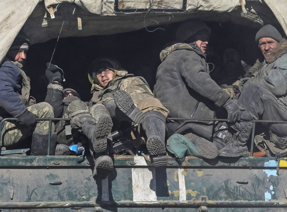 Weary Ukrainian servicemen leave the area around the besieged town of Debaltseve in eastern Ukraine on Wednesday after fierce combat with pro-Russian rebels