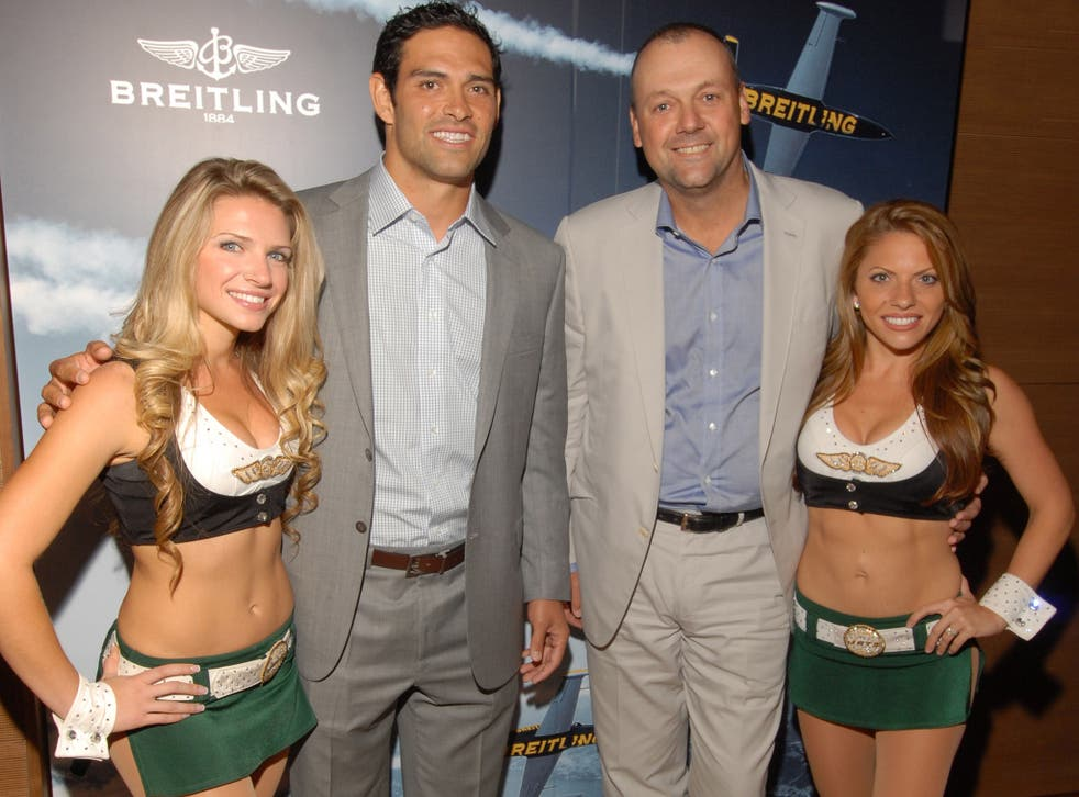 Breitling president Thierry Prissert (second from right) poses with NFL quarterback Mark Sanchez and two cheerleaders in New York in 2012