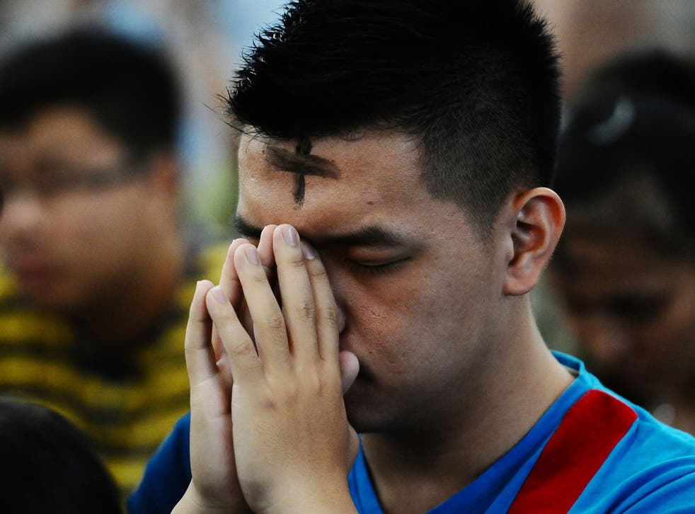 A Catholic man prays during the Ash Wednesday ceremony at Roh Kudus Church on March 5, 2014 in Surabaya, Indonesia.
